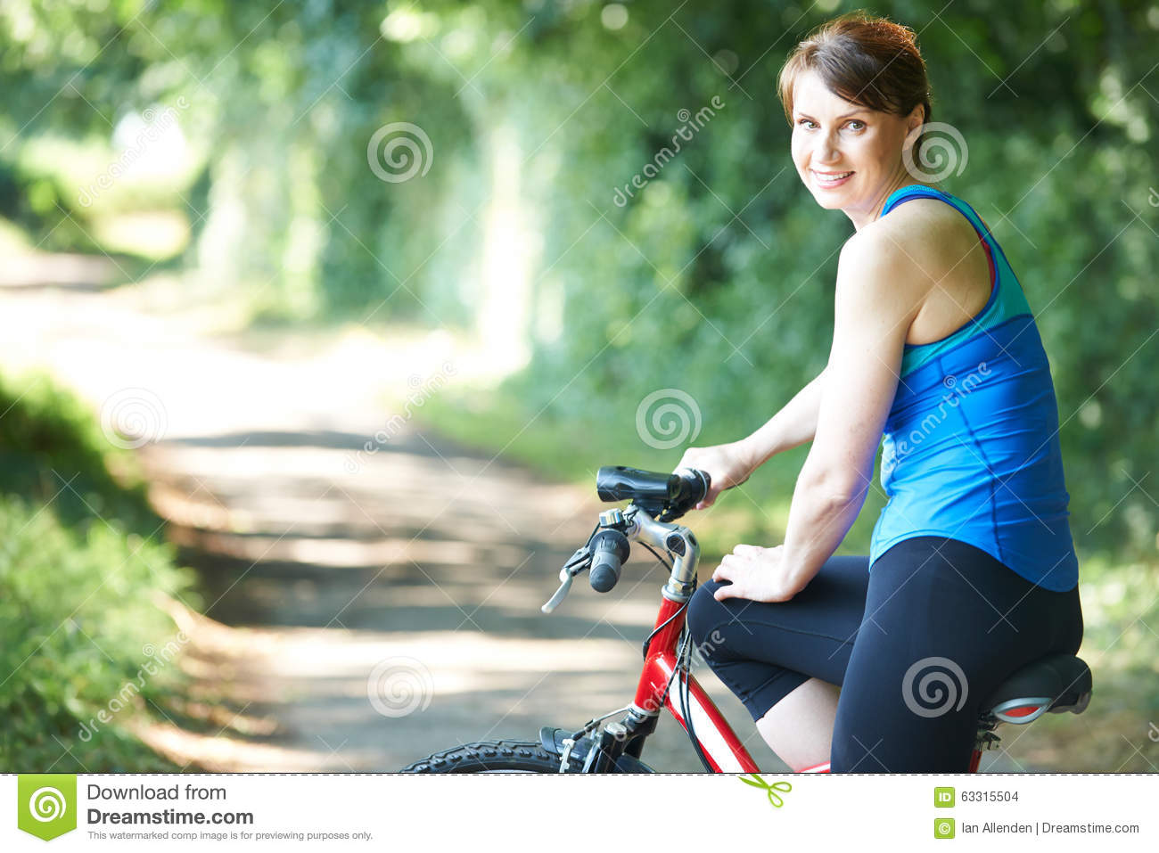 middle aged woman cycling along country road stock photo - image of