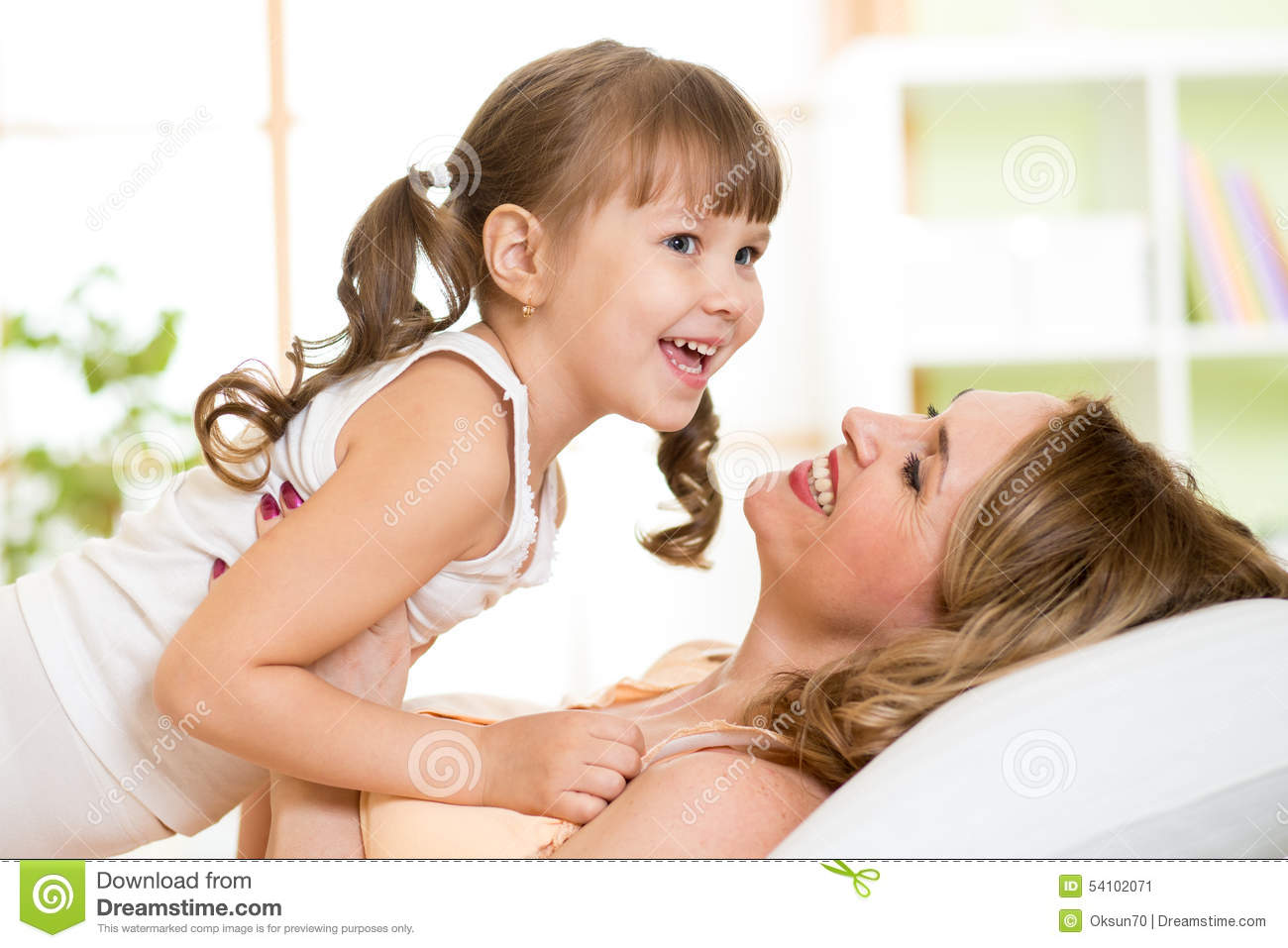Middle-aged woman with her daughter child play and