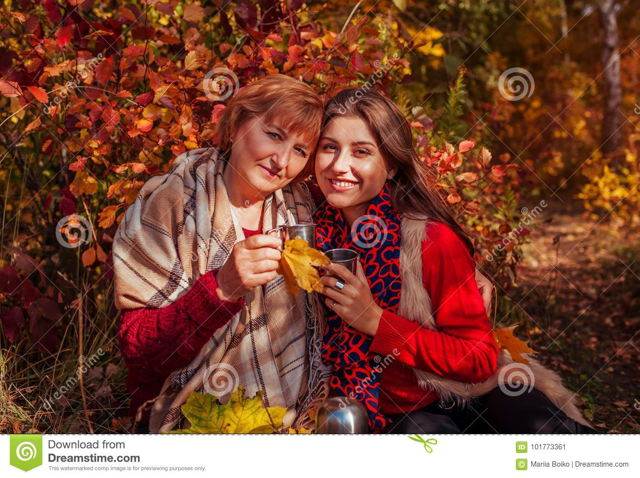 Middle-aged woman and her daughter having tea in the forest