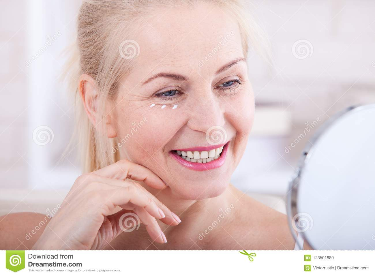 Middle aged woman looking at wrinkles in mirror. Plastic surgery and collagen injections. Makeup