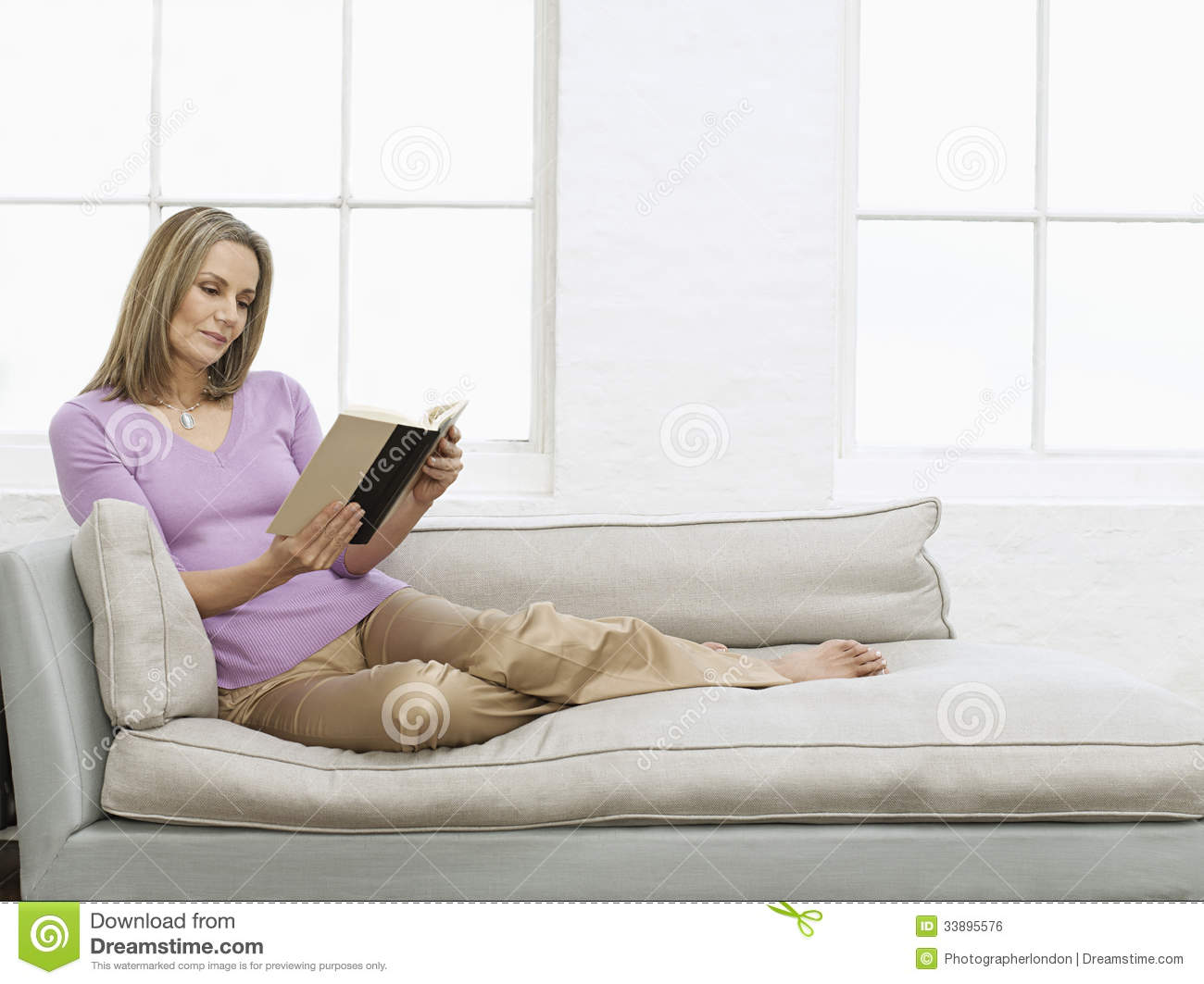 18a85e7489a9 Middle Aged Woman Reading Book On Sofa Stock Photo - Image of ...