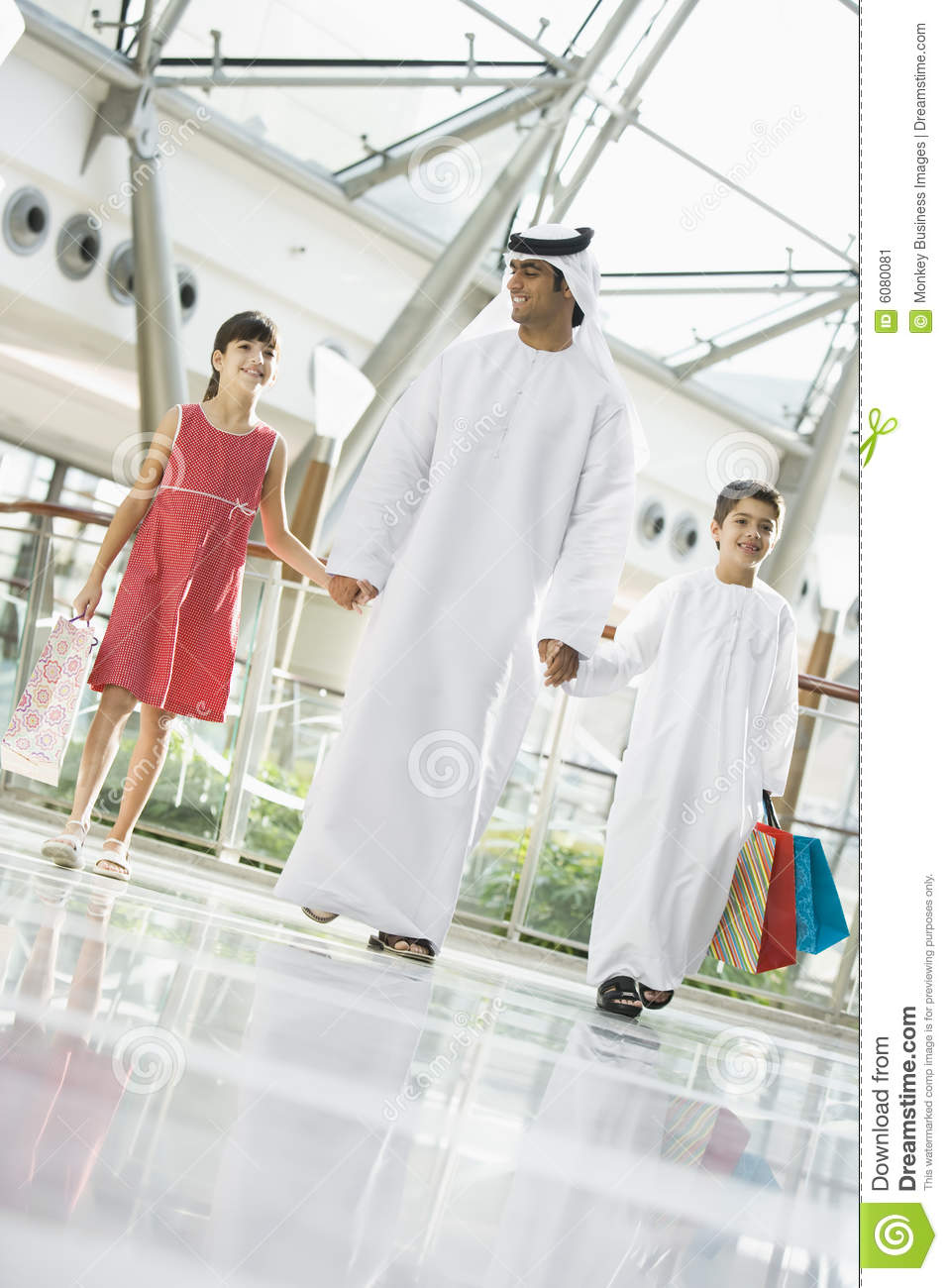 A Middle Eastern man with two children shopping