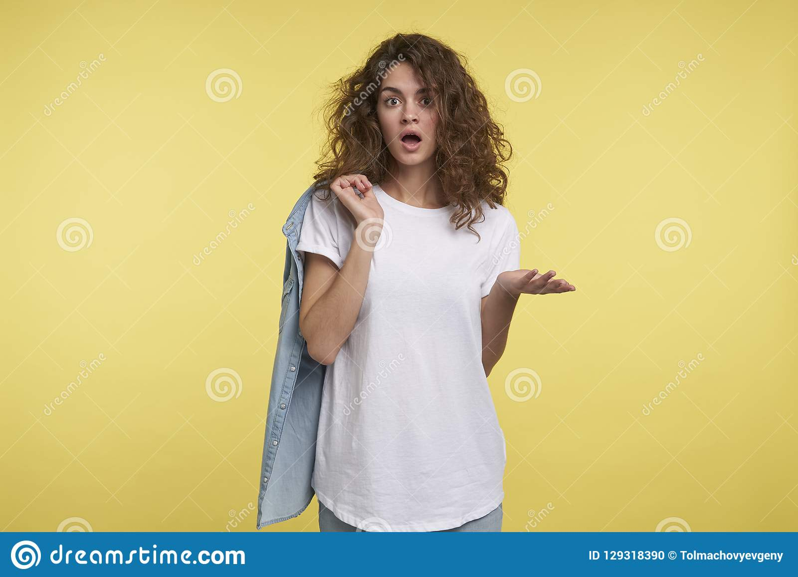 Midium shot of young surprised woman with curly hair