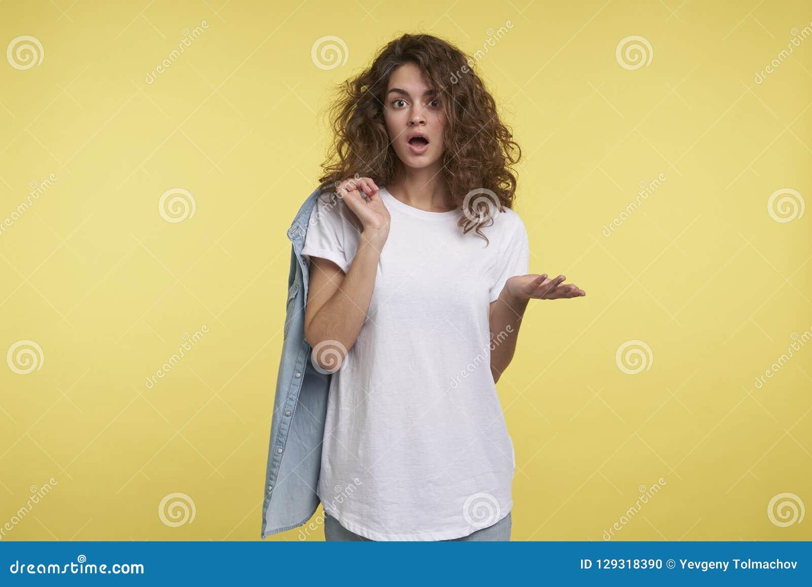 Midiumschot van jonge verraste vrouw met krullend haar