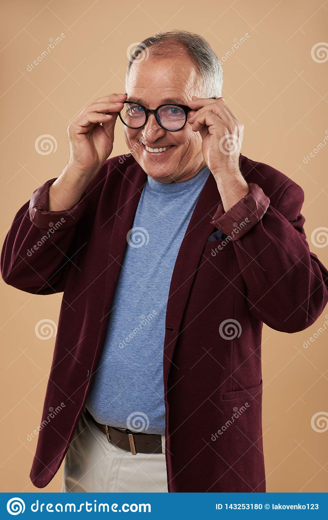 Midja upp av den positiva mannen som bär runda exponeringsglas och att le