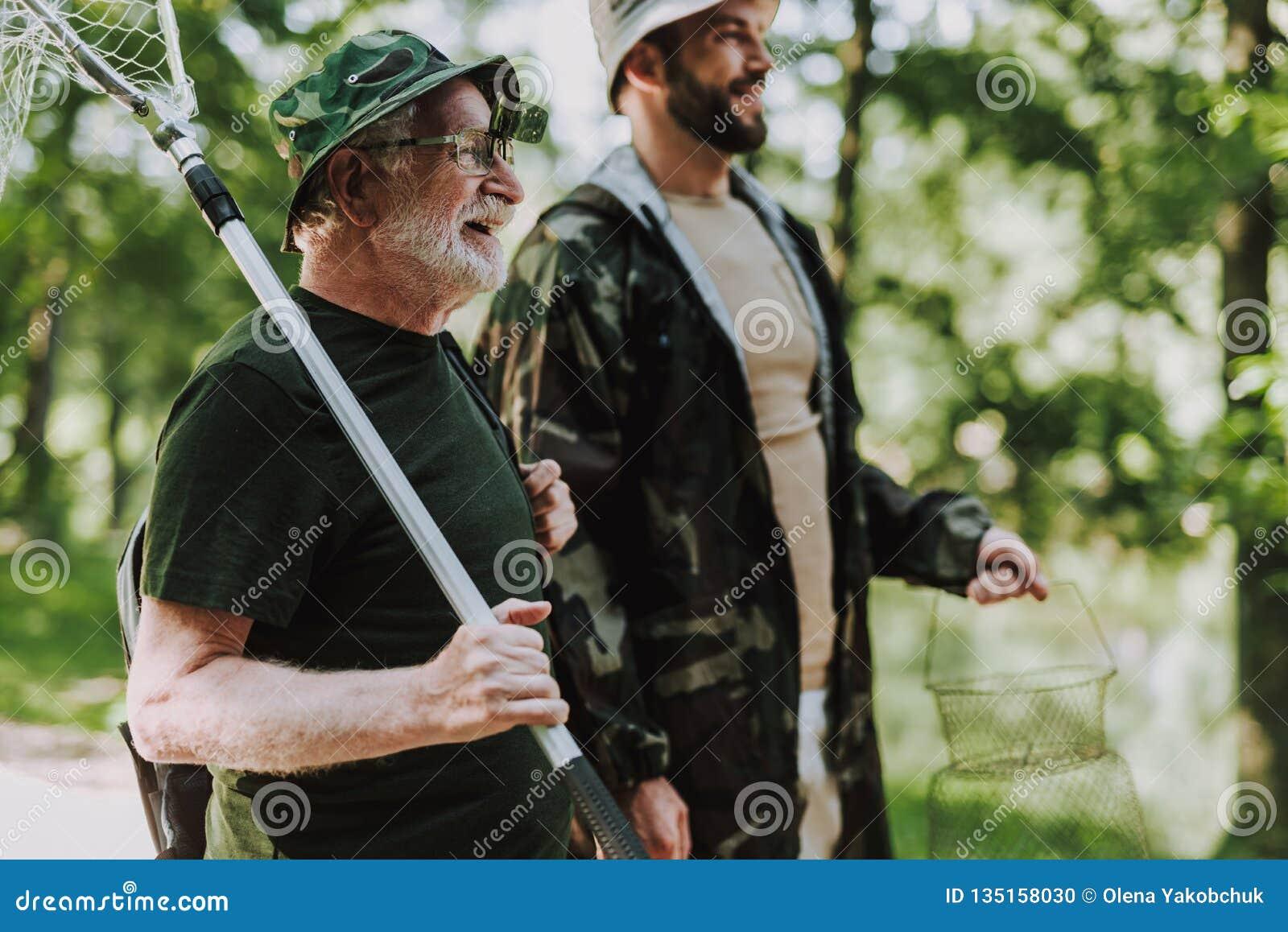 Midja upp av en le man som förbereder sig för att fiska med hans son