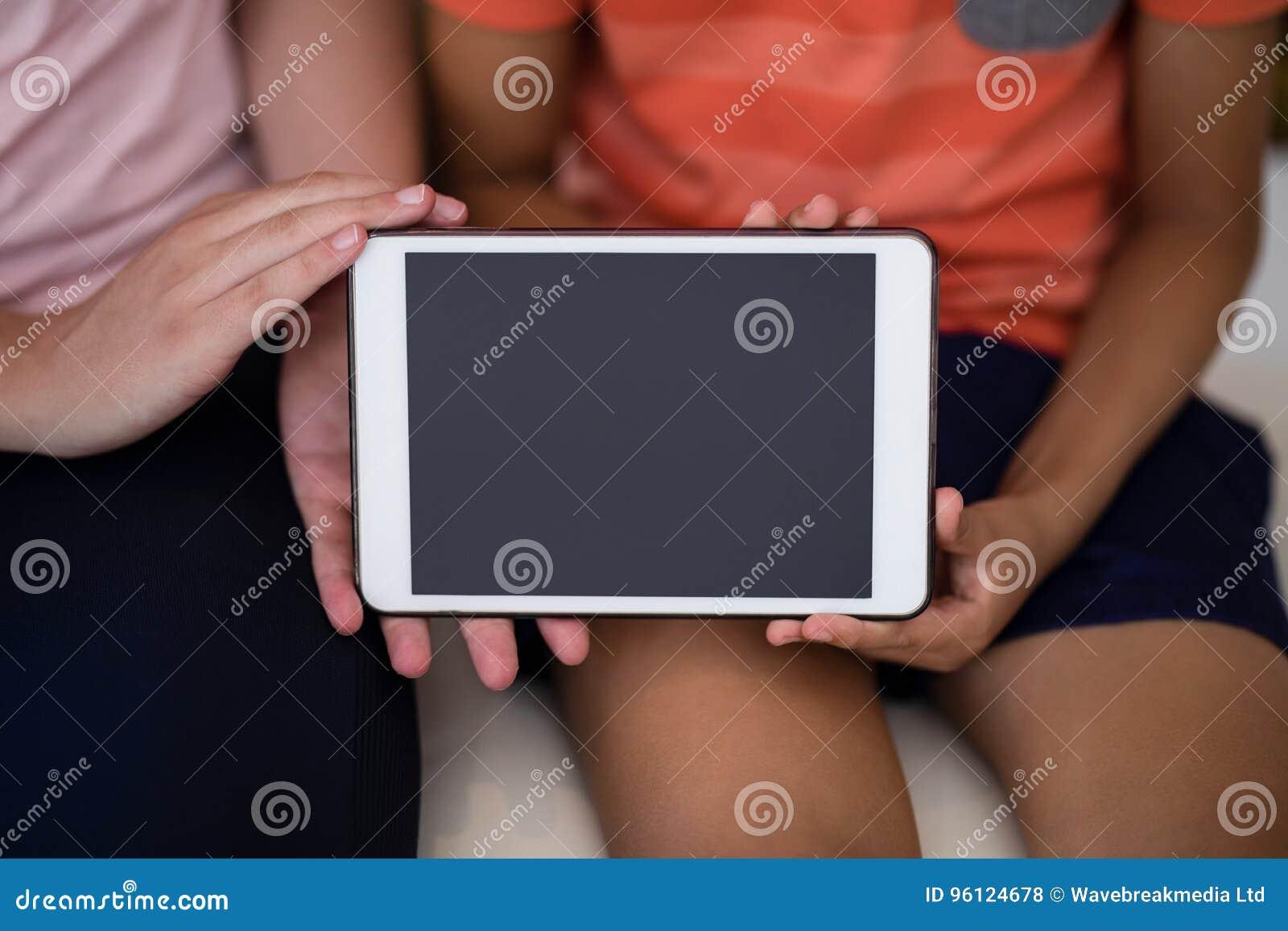 Midsection żeński terapeuta i chłopiec pokazuje cyfrową pastylkę podczas gdy siedzący na łóżku