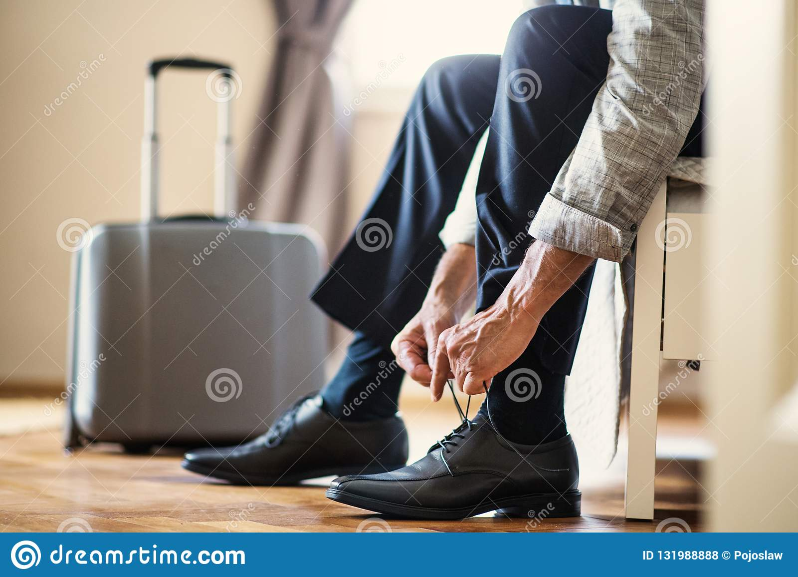 Midsection av affärsmannen på en affärstur som sitter i ett hotellrum som binder skosnöre