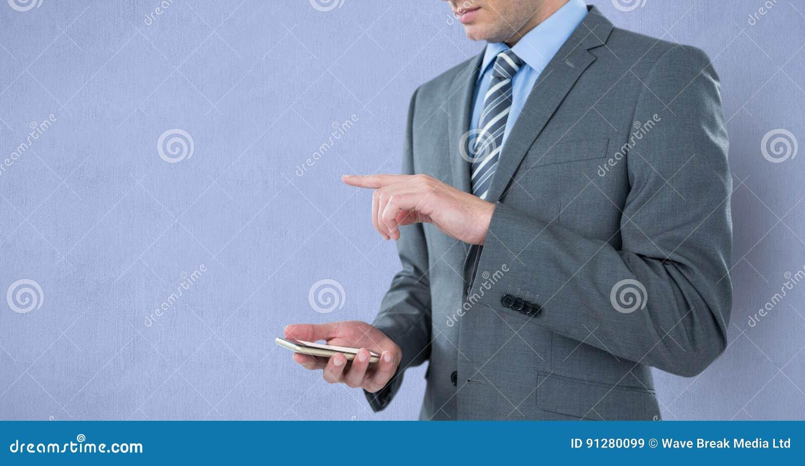 Midsection av den hållande mobiltelefonen för affärsman, medan göra en gest över purpurfärgad bakgrund