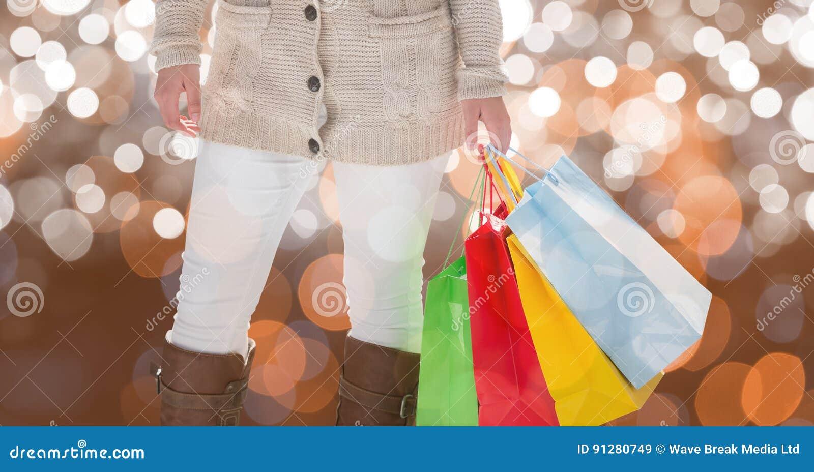 Midsection av kvinnan som rymmer färgrika shoppingpåsar
