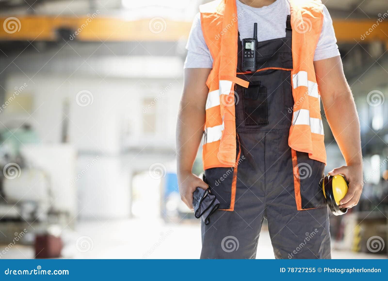 Midsection av unga örabeskyddanden och handskar för manuell arbetare hållande i metallbransch