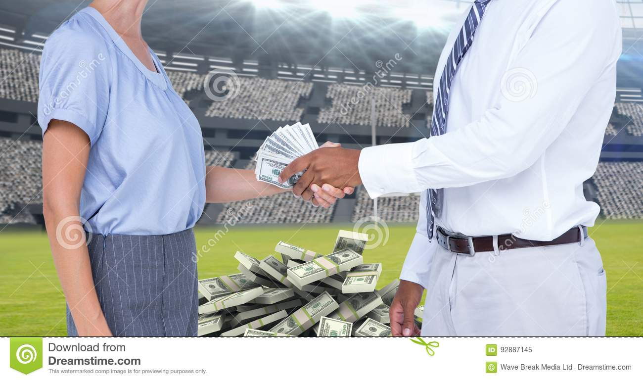 Midsection of business people exchanging money at football stadium representing corruption