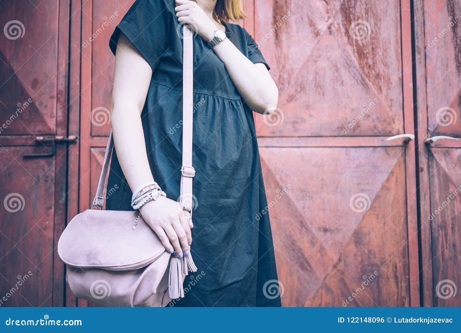 Midsection de una mujer que sostiene un bolso