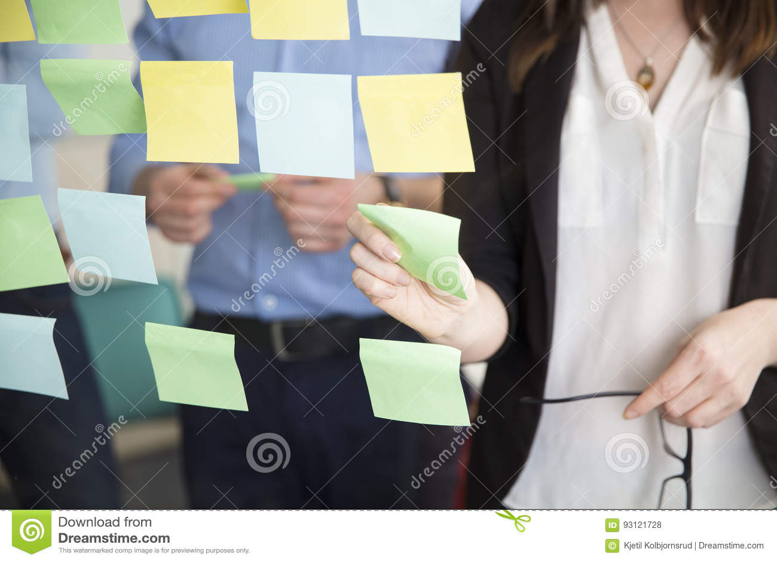 Midsection del dirigente facente una pausa di Sticking Note While della donna di affari