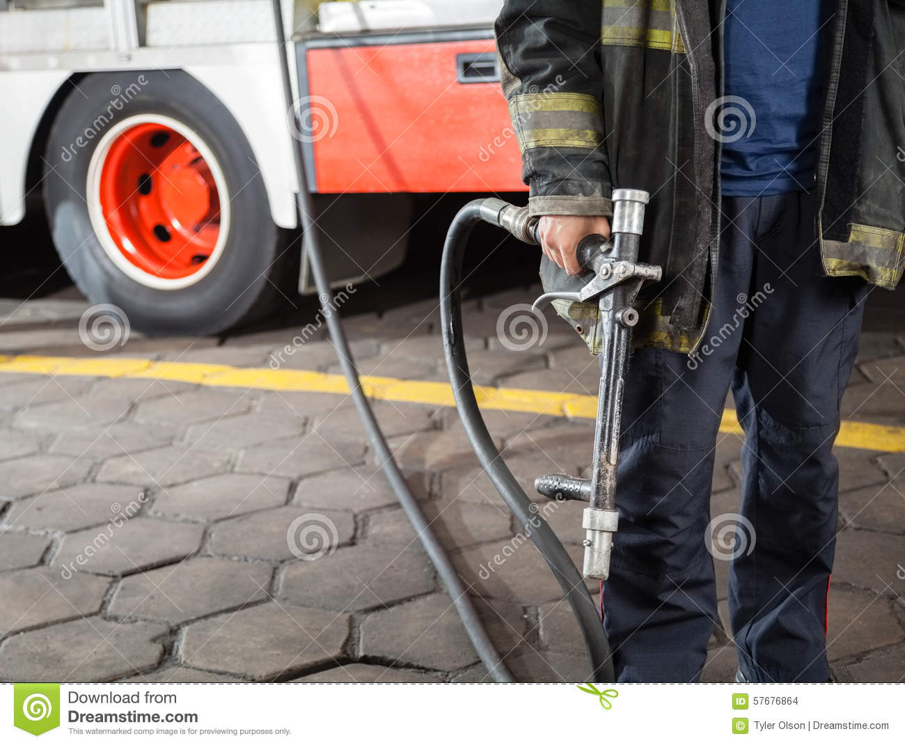 Midsection del pompiere Holding Water Hose