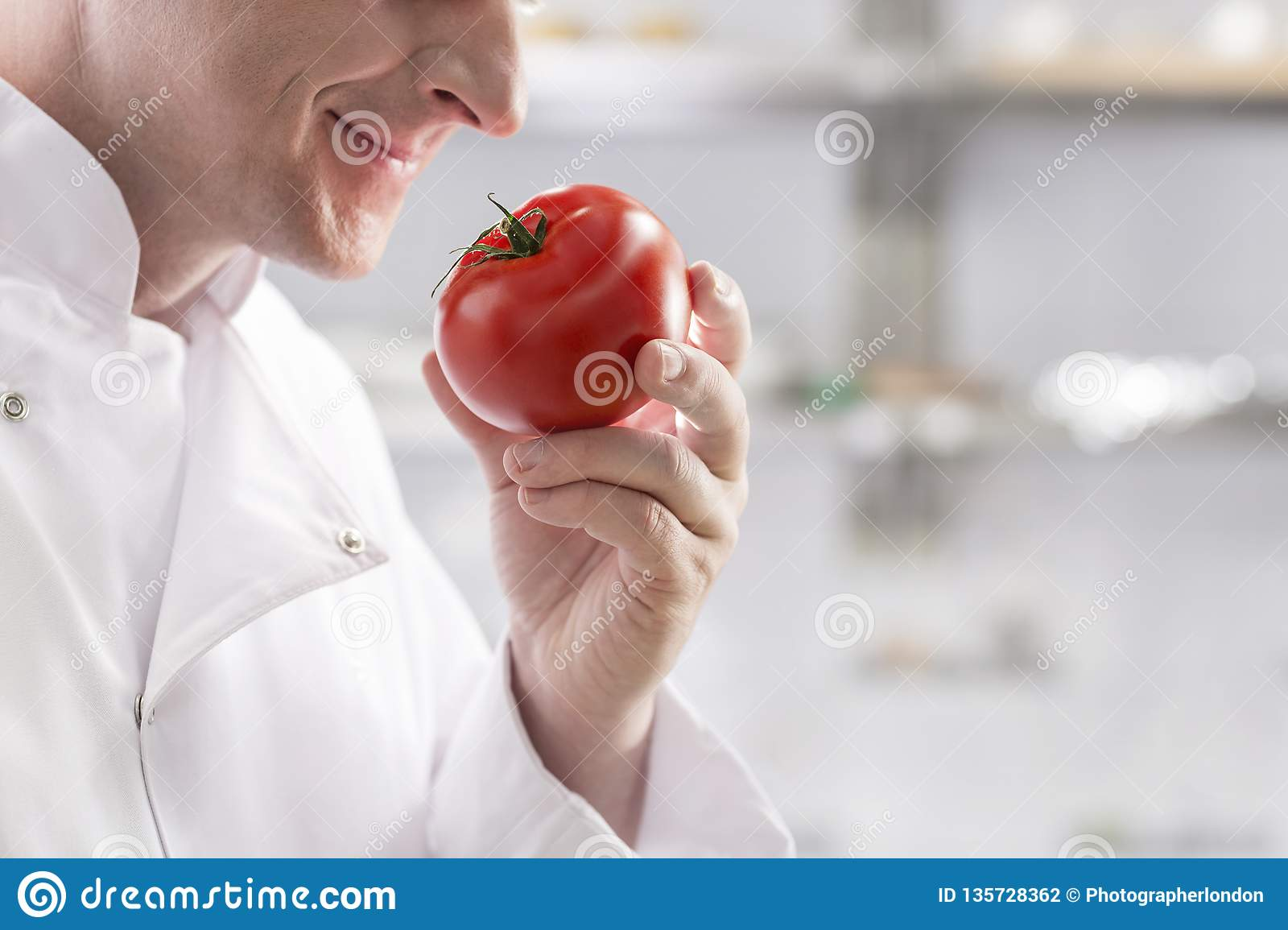 Midsection of mature chef smelling fresh red tomato while standing at restaurant kitchen