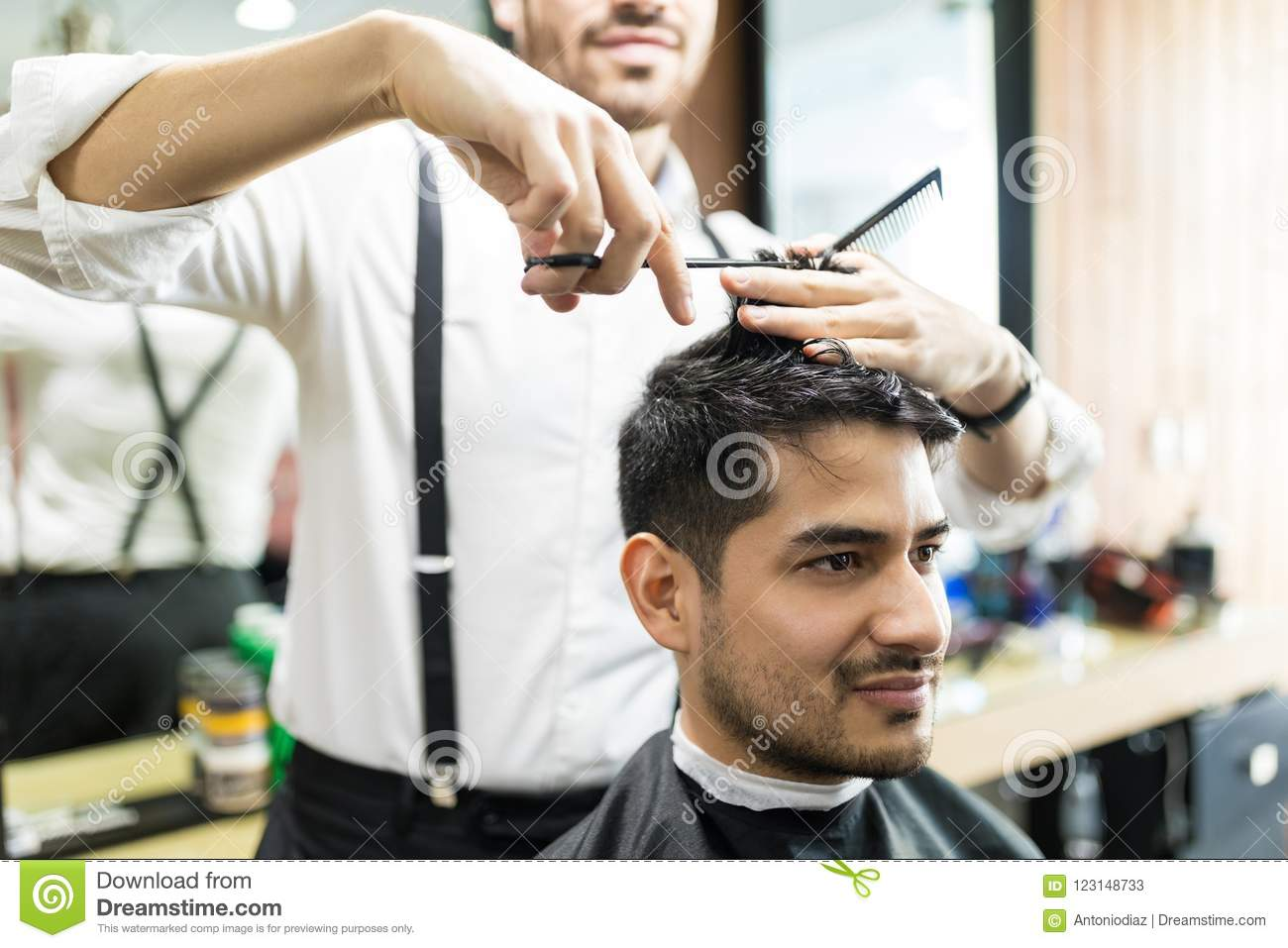 Professional Barber Giving Haircut To Male In Shop