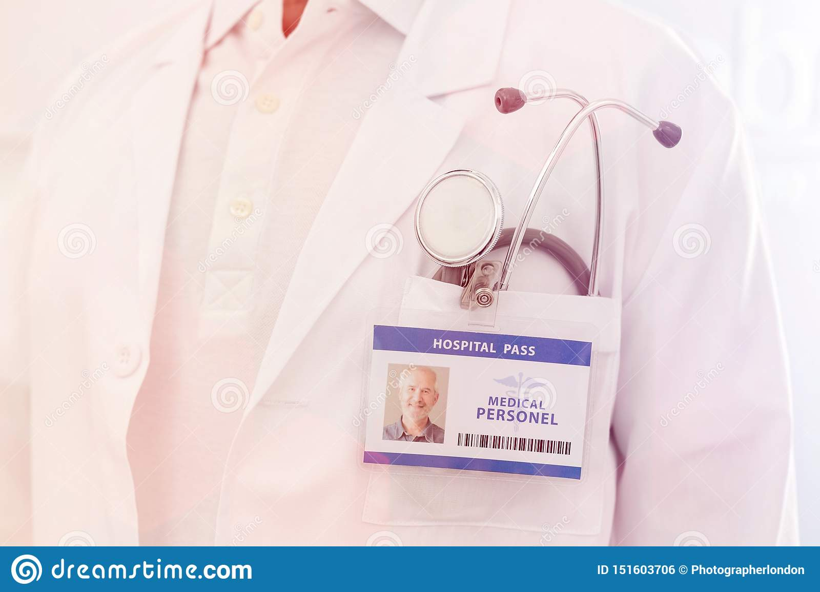 Midsection of senior doctor with identity card and stethoscope at hospital