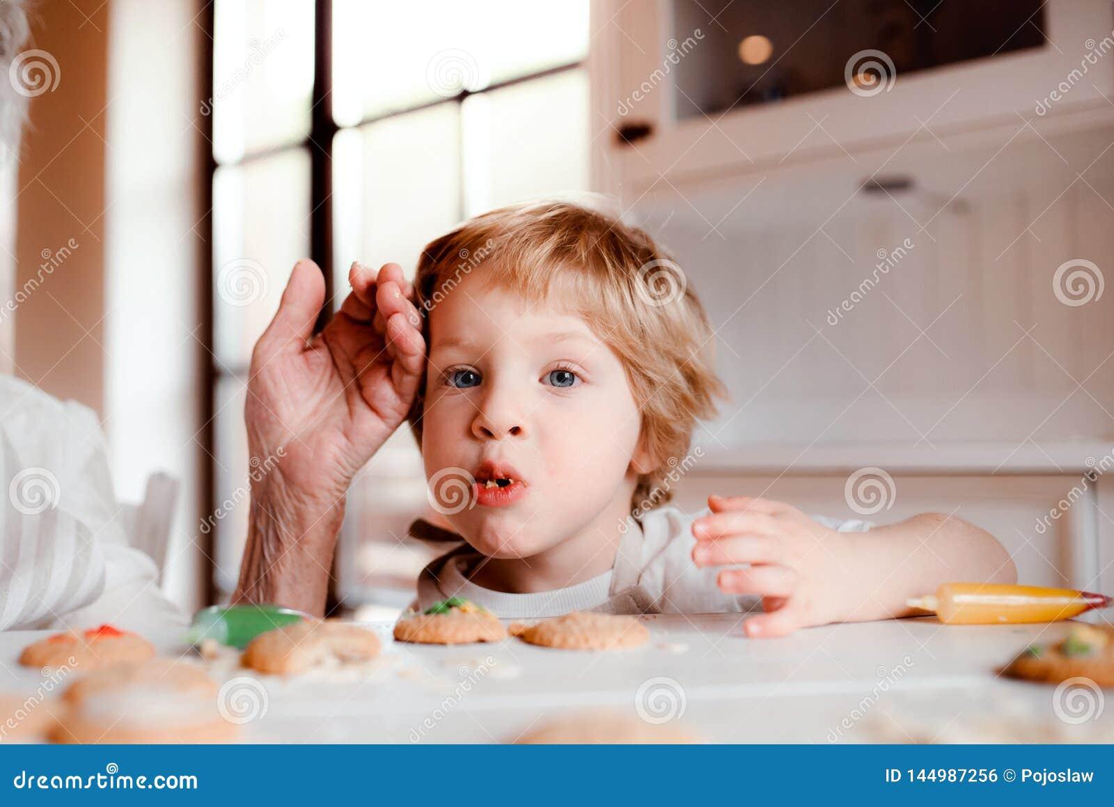 Midsection van hogere grootmoeder met het kleine peuterjongen maken koekt thuis