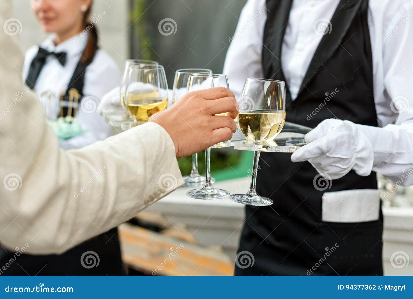 Midsection van professionele kelner in eenvormige dienende wijn tijdens de partij van de buffetcatering, feestelijk gebeurtenis o