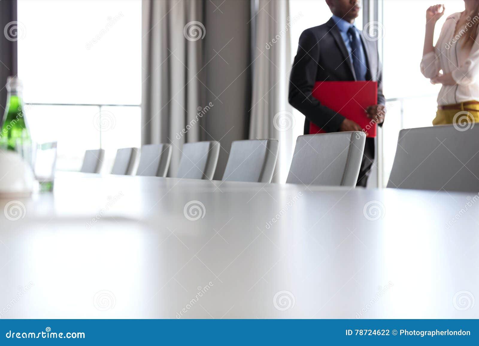 Midsection van zakenman en onderneemster die zich door conferentielijst bevinden in bureau