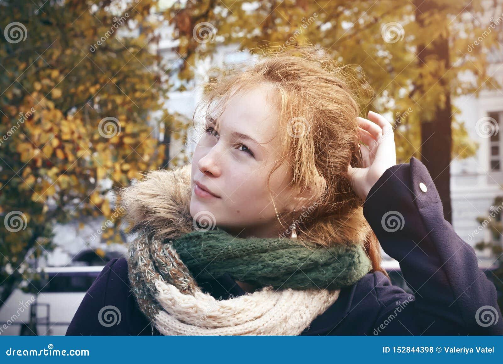 Miedzianowłosa dziewczyny pozycja po środku miasto parka w jesieni