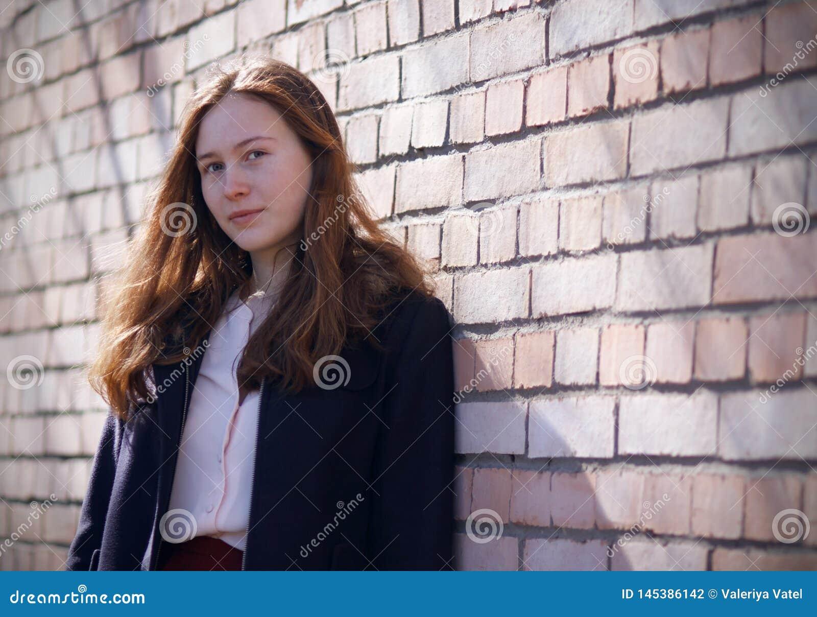 Miedzianowłosi dziewczyna stojaki blisko ściany z cegieł