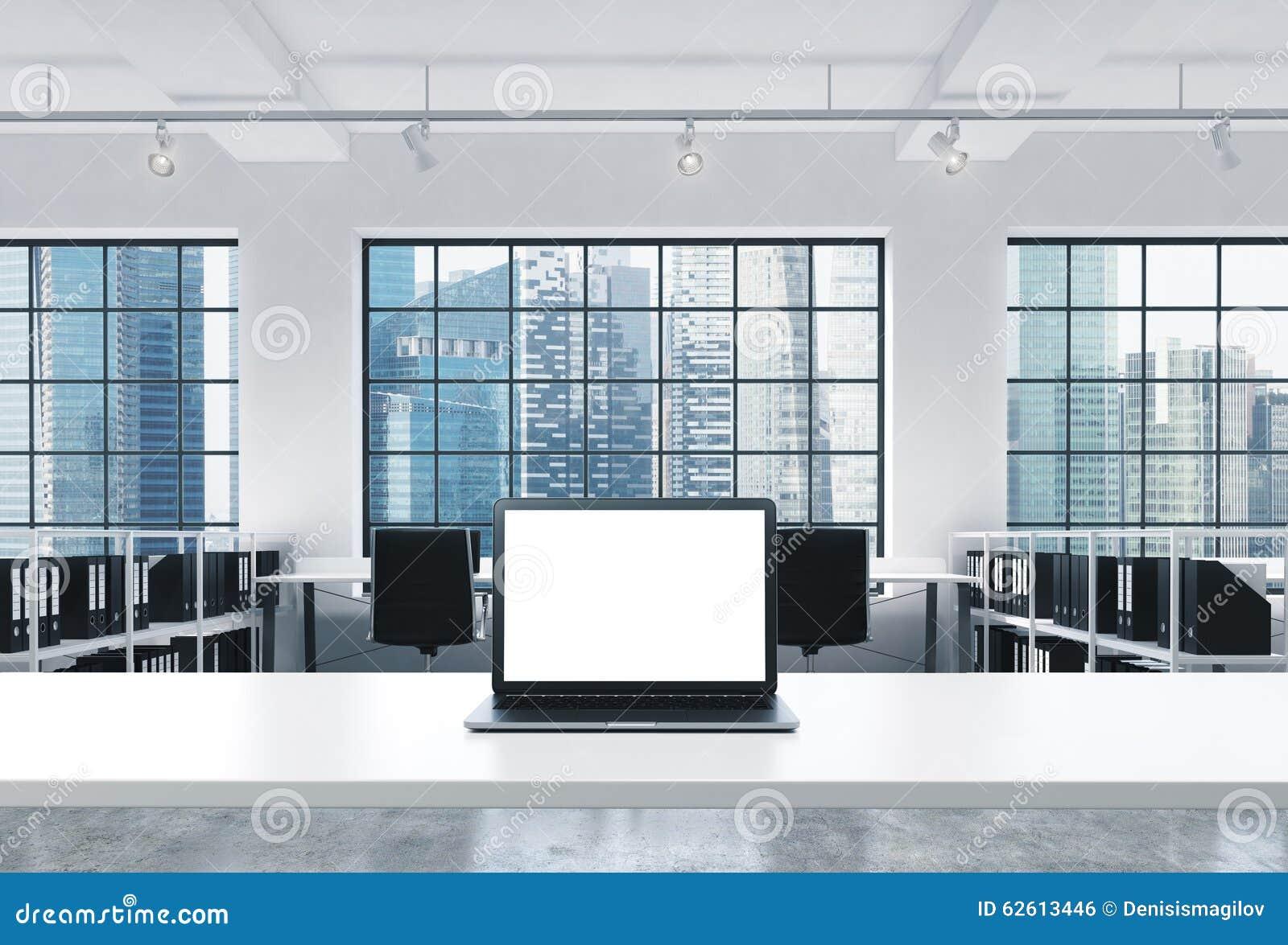 Miejsce pracy w jaskrawym nowożytnym loft otwartej przestrzeni biurze Pracujący biurko wyposaża z nowożytnym laptopem z biel kopi
