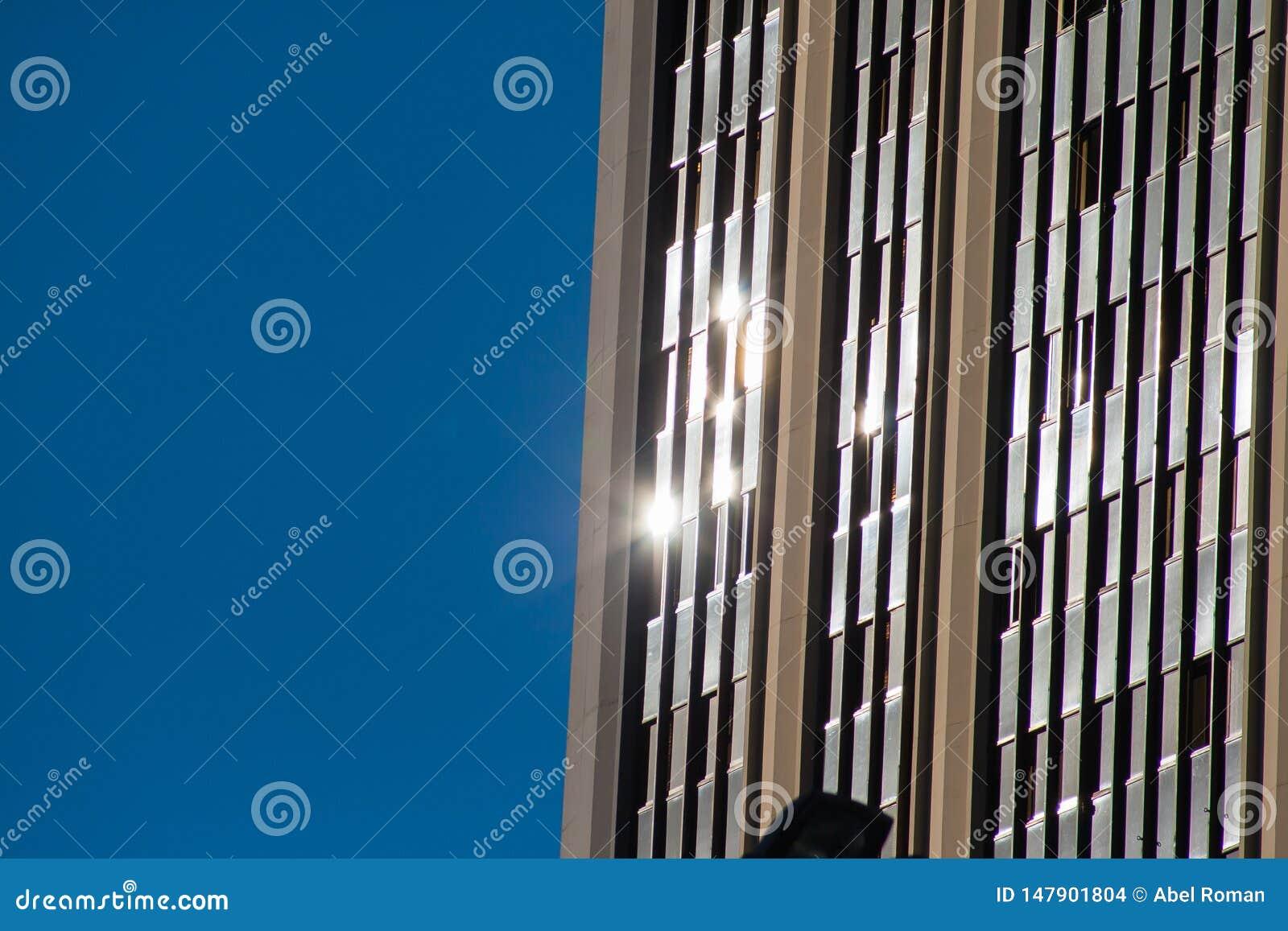 Miejskie odbicia Sunbeams odbijali na szkle budynek z błękitnym tłem