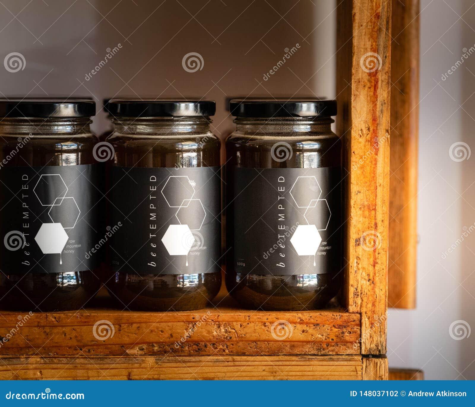 Miel dans des pots en verre avec les couvercles noirs à vendre sur des étagères de magasin faites de vieilles ruches d abeille