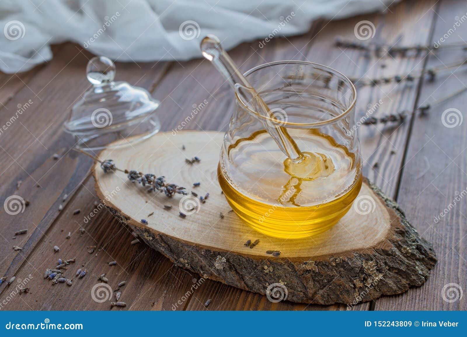 Miel dans le pot en verre avec le plongeur de miel sur le fond en bois rustique