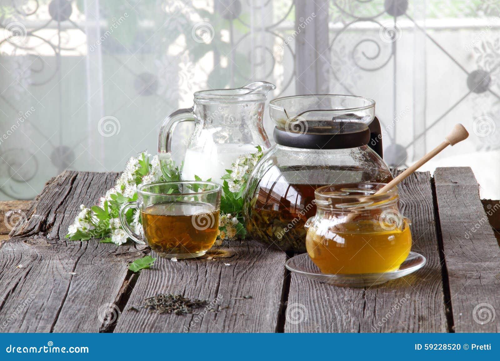 Miel en el banco transparente, la leche en un jarro y el té en un transparen