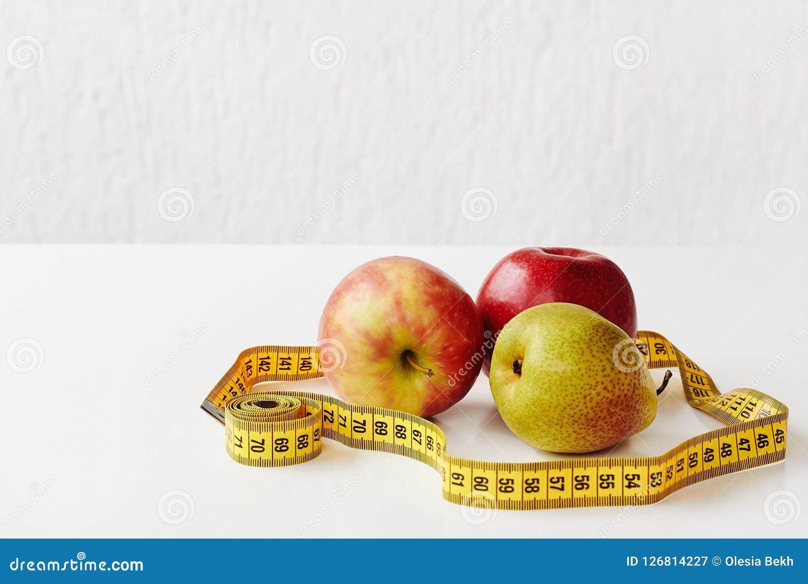 Mierzy taśmy i świeżych owoc jabłka, bonkreta na białym tle Strata ciężar, szczupły ciało, zdrowej diety pojęcie