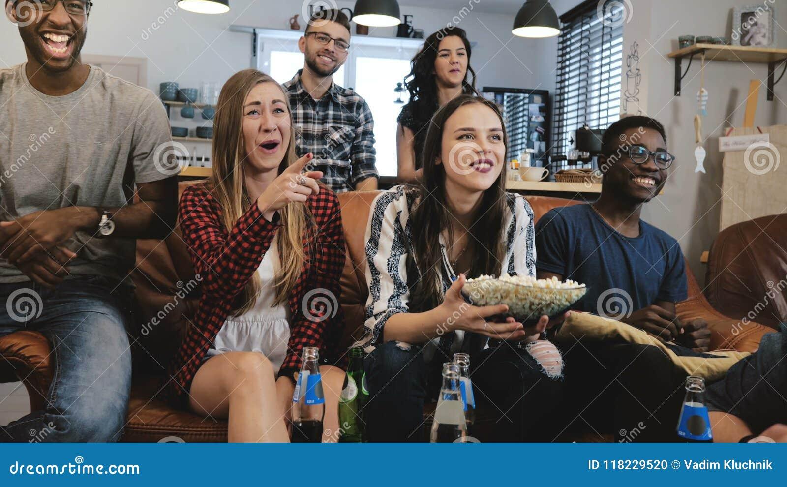 Mieszany pochodzenie etniczne grupy dopatrywanie bawi się grę na TV Emocjonalni fan na leżance z napojów i przekąsek 4K zwolnione