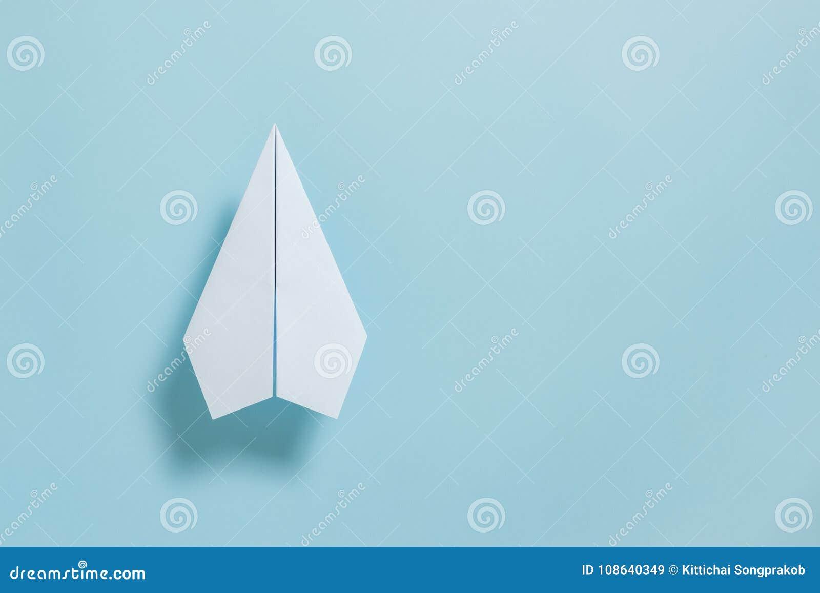 Mieszkanie nieatutowy białego papieru samolot na pastelowym błękitnym koloru tle
