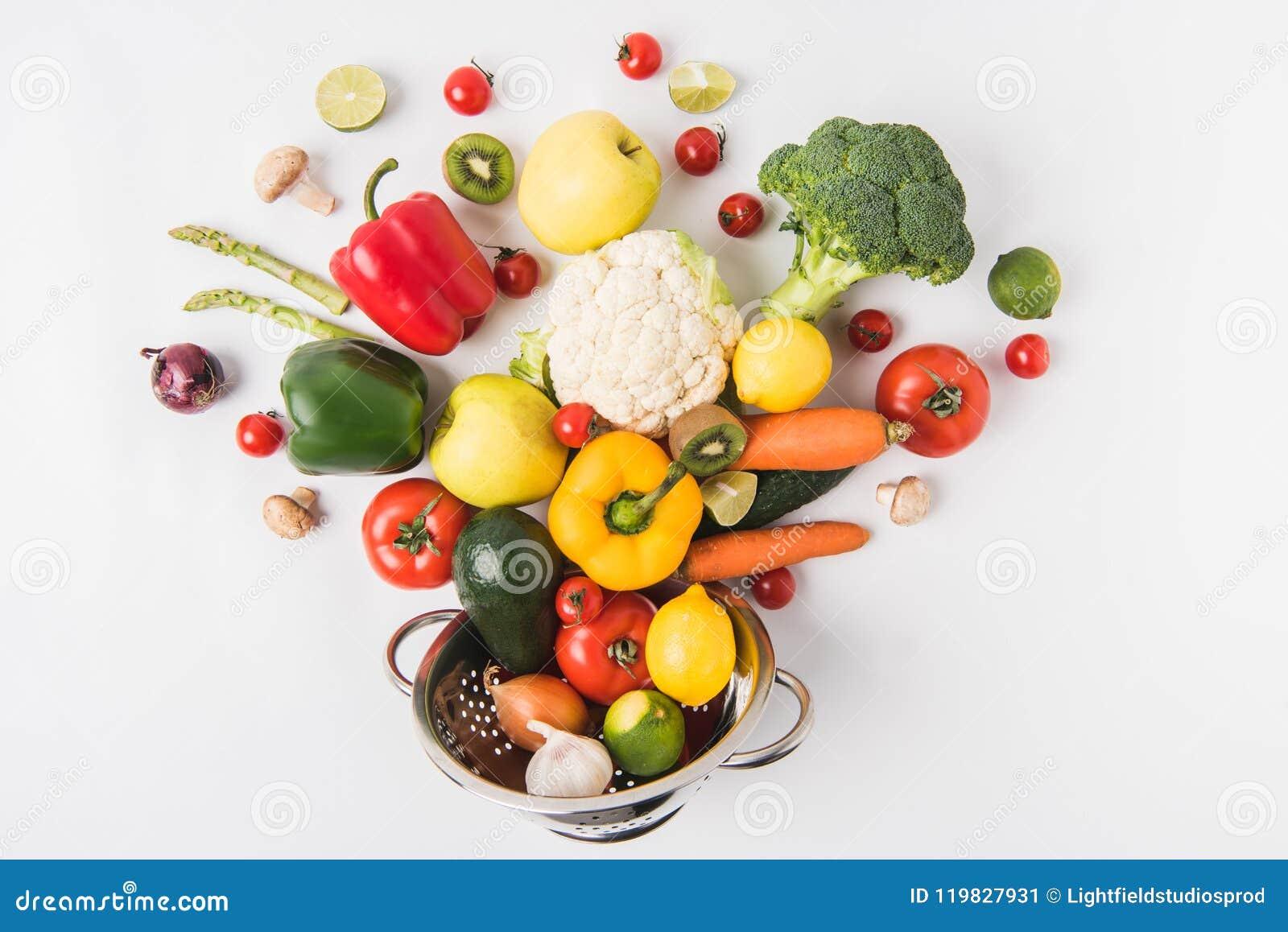 Mieszkanie nieatutowy skład kolorowi warzywa i owoc w colander odizolowywającym na białym tle