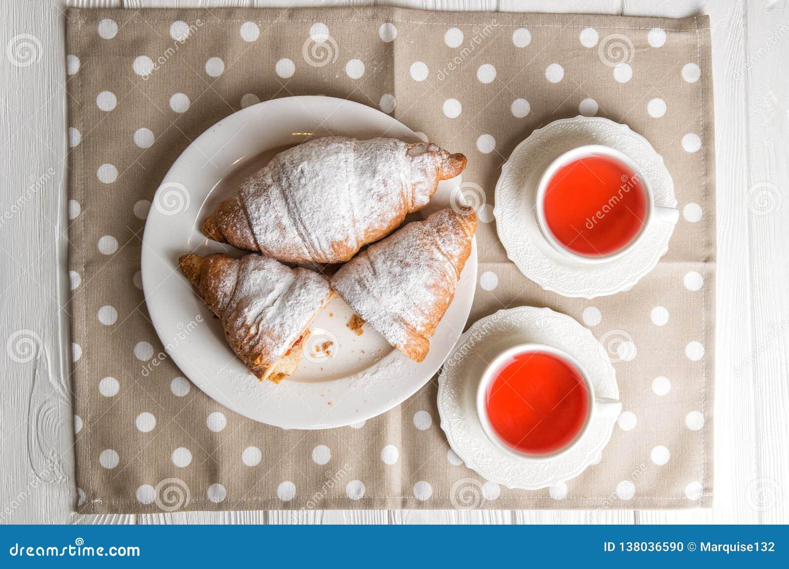 Mieszkanie nieatutowy, zamyka up Romantyczny śniadanie dla dwa Świeżo piec Francuscy croissants i jagodowa herbata Jeden croissan