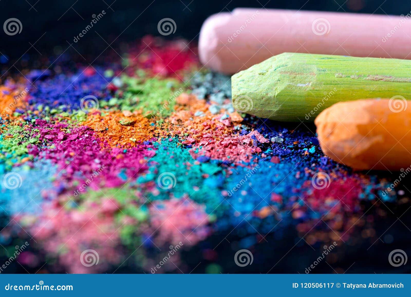Miettes de craie multicolore sur un fond noir Joie, carnaval, panorama Un jeu pour des enfants Art