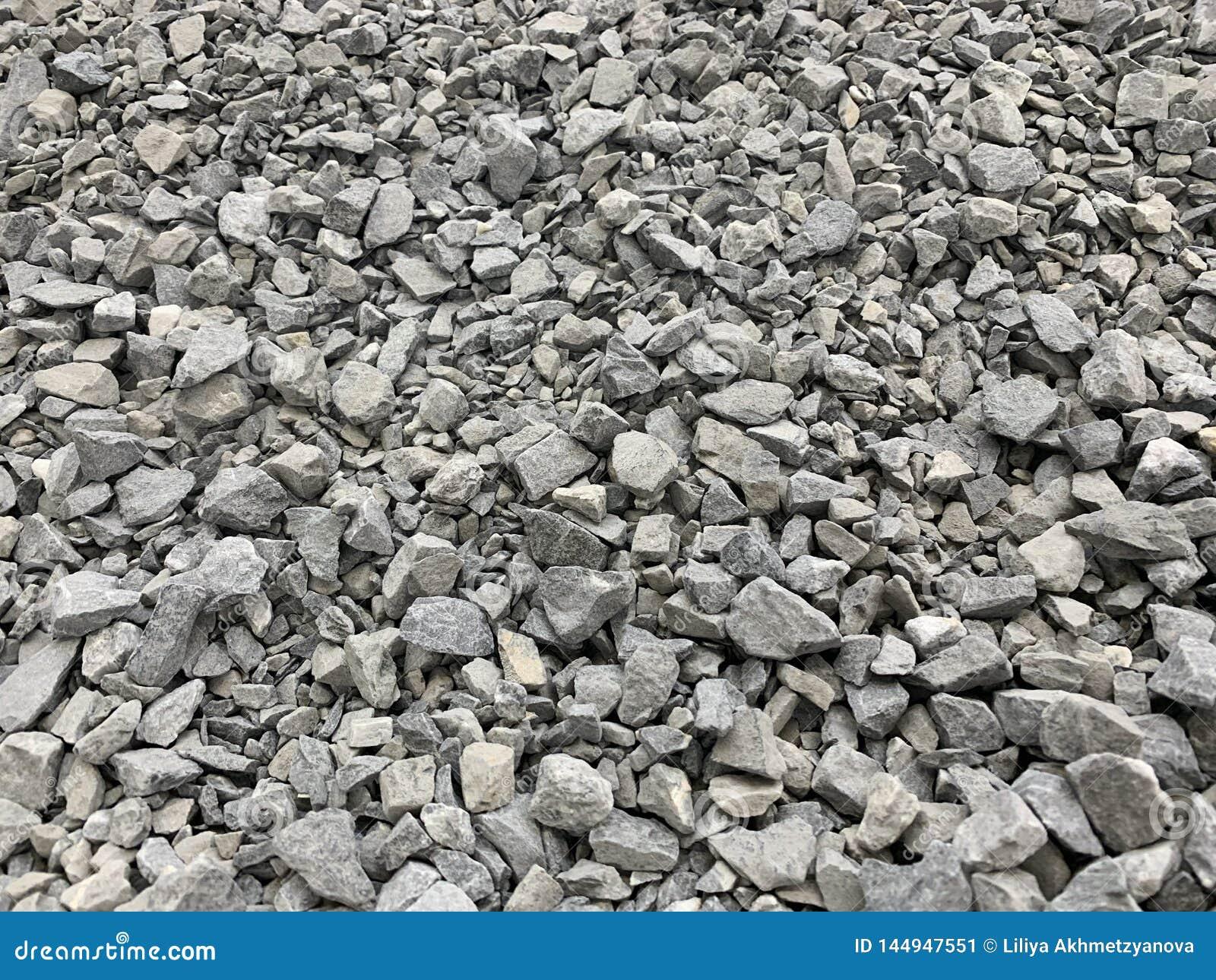 Migalha pequena cinzenta do granito, material de construção, fundo simples