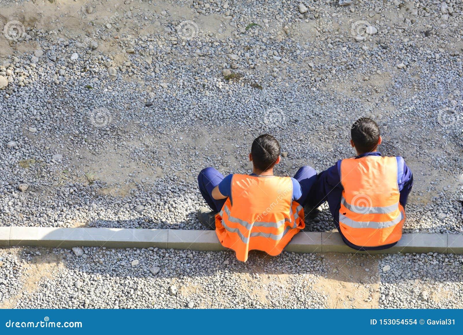 Migrantarbetare i gula och orange västar som vilar vid vägen De sitter på sidlinjerna reparera v?gen kopiera avst?nd
