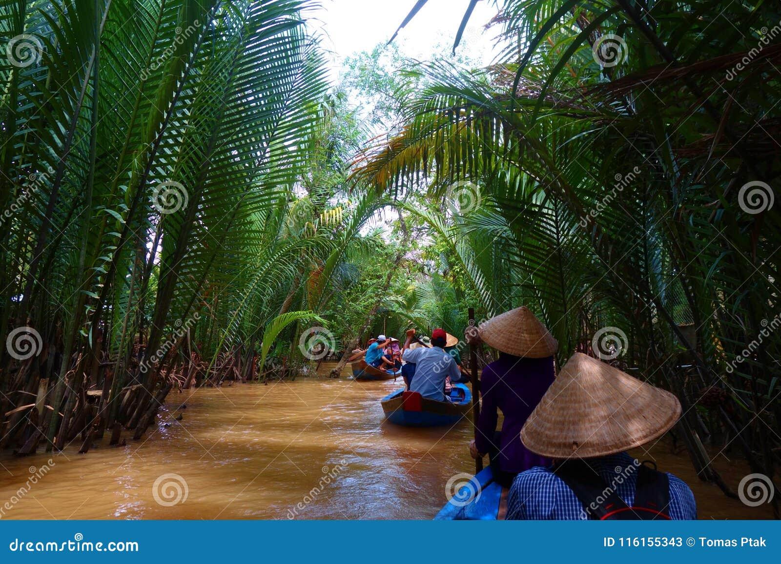 Mijn Tho, Vietnam: Toerist bij Mekong cruise van de Rivier de Deltawildernis met niet geïdentificeerde craftman en vissers het ro