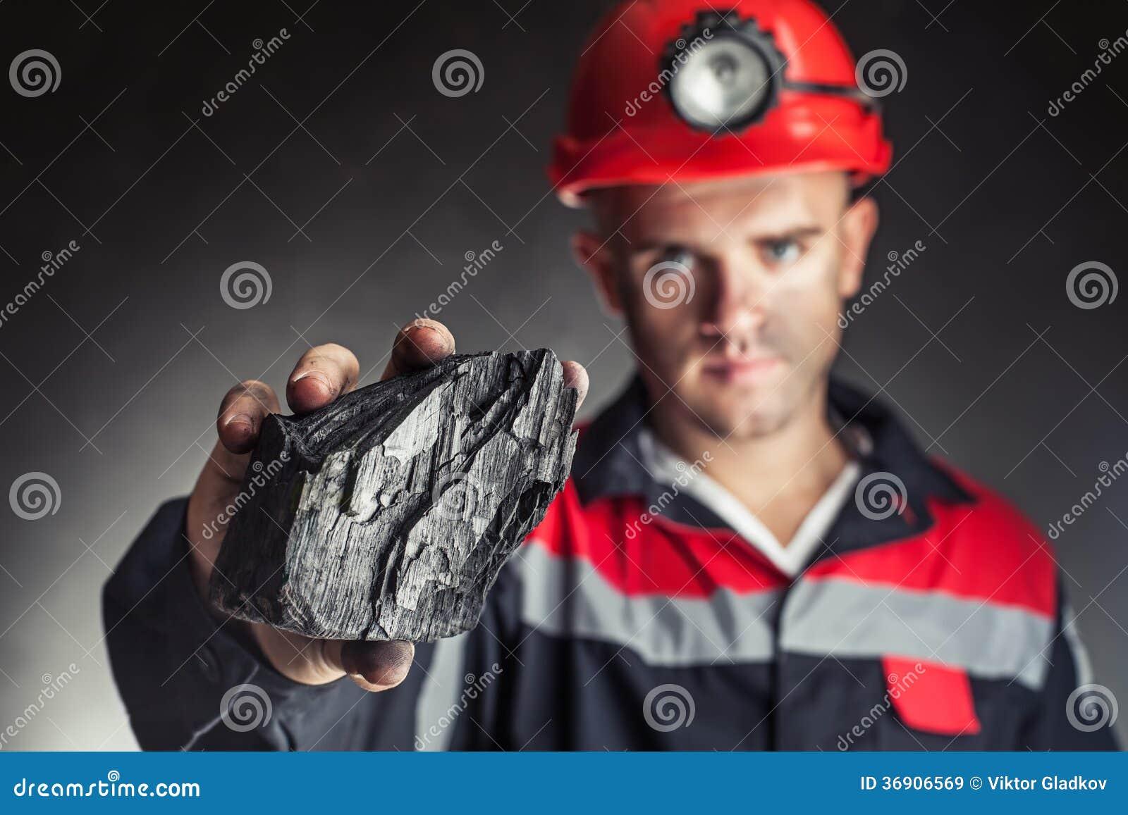 Mijnwerker die stuk van steenkool tonen