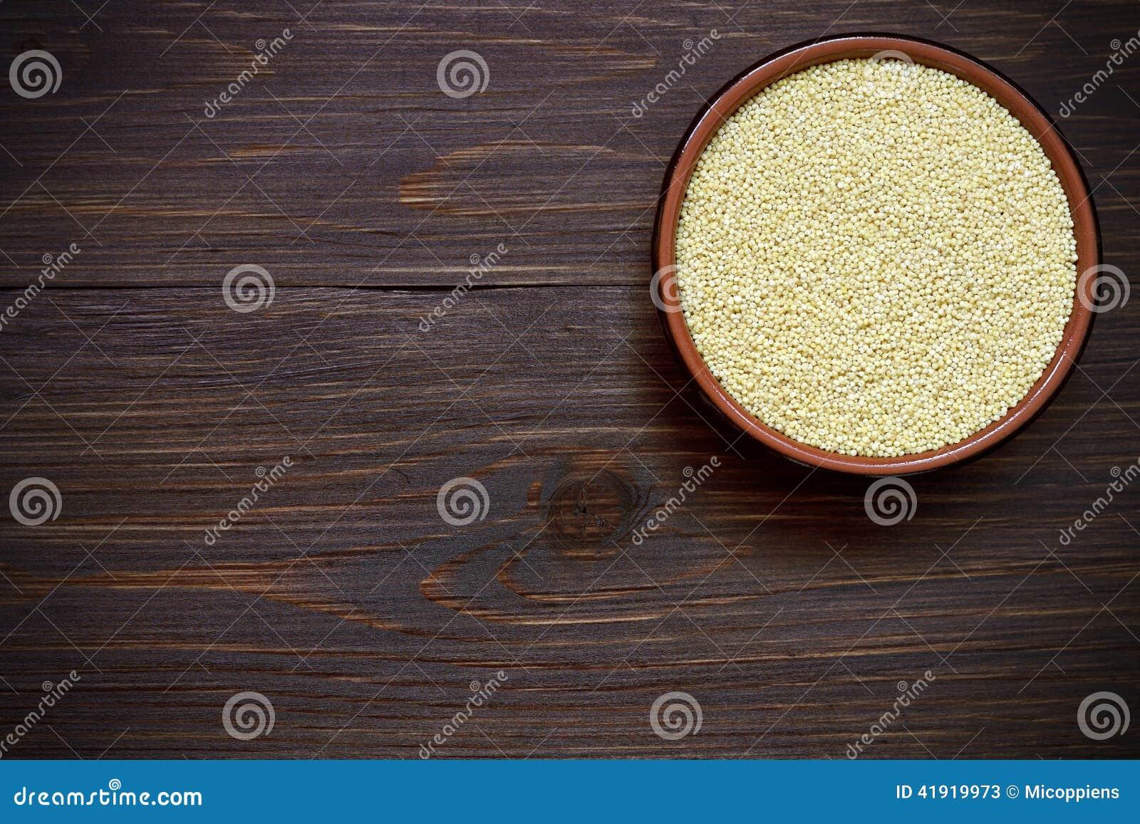 Mijo orgánico en cuenco en la tabla de madera