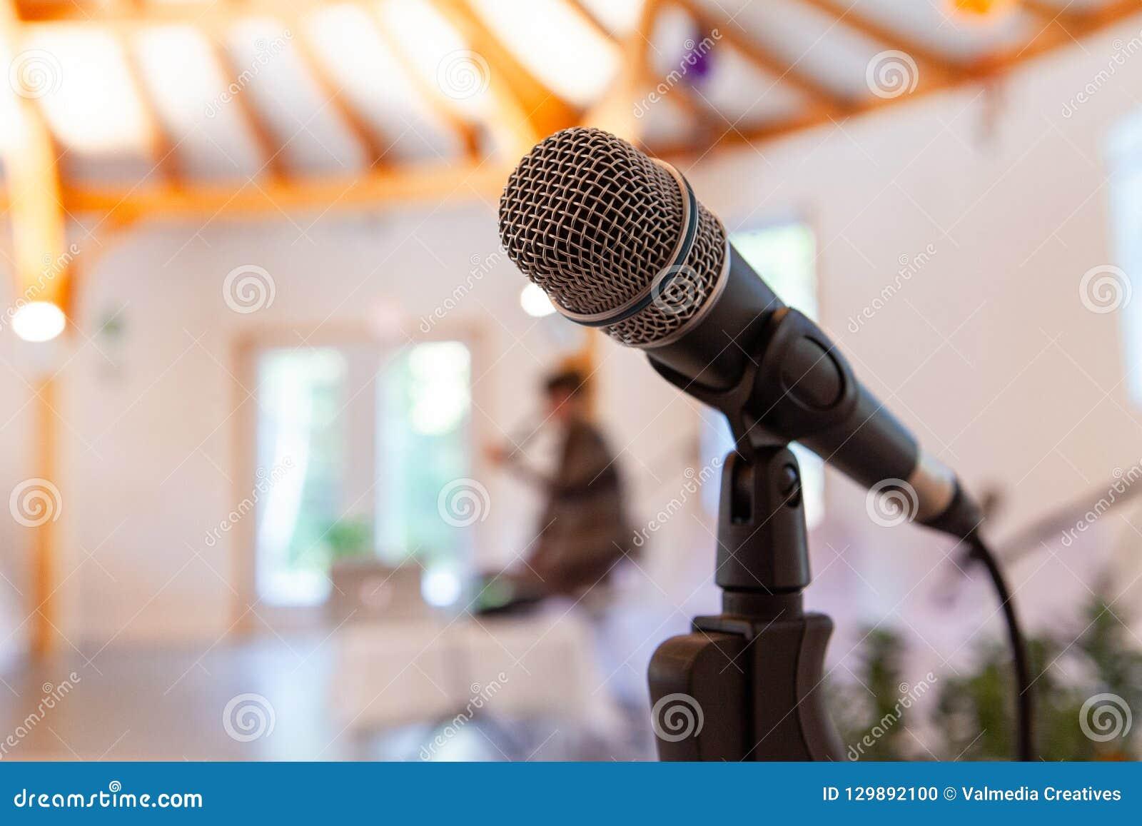 Mikrofon auf einem geraden Stand, wenn die undeutliche Frau eine Konferenz gibt