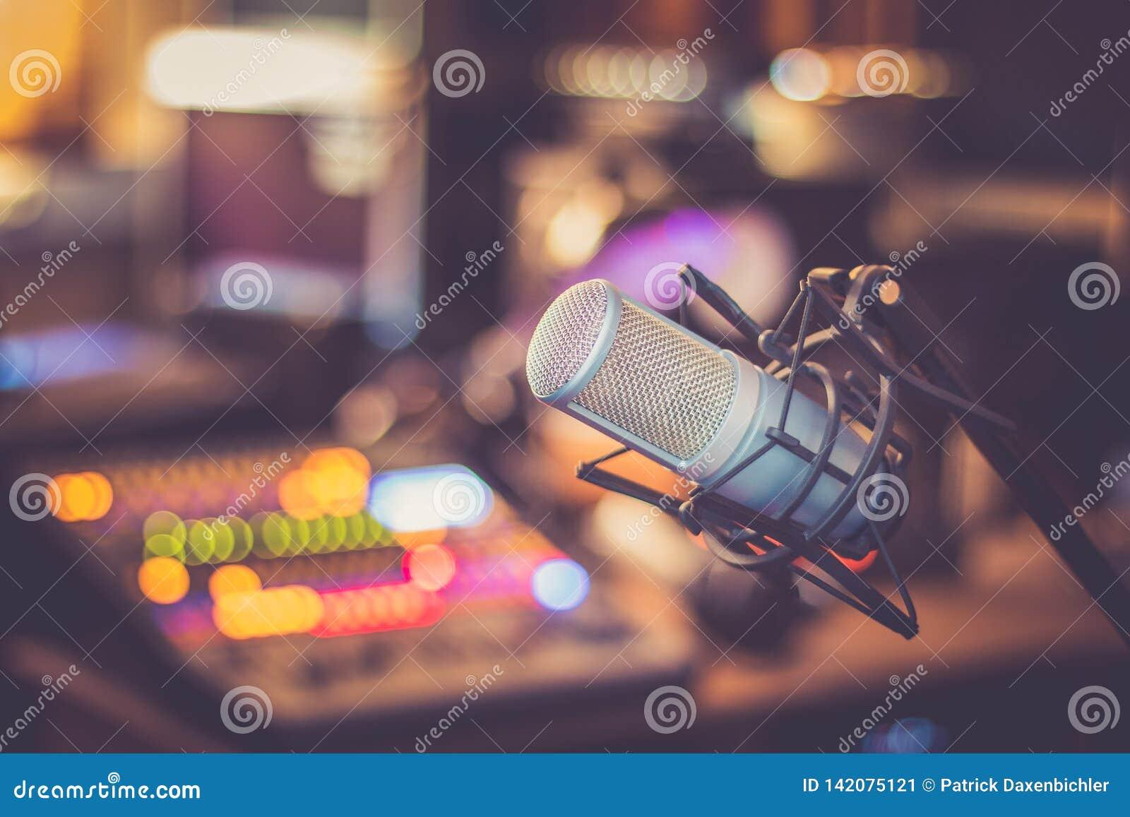 Mikrofon i en yrkesmässig inspelning- eller radiostudio, utrustning i den oskarpa bakgrunden