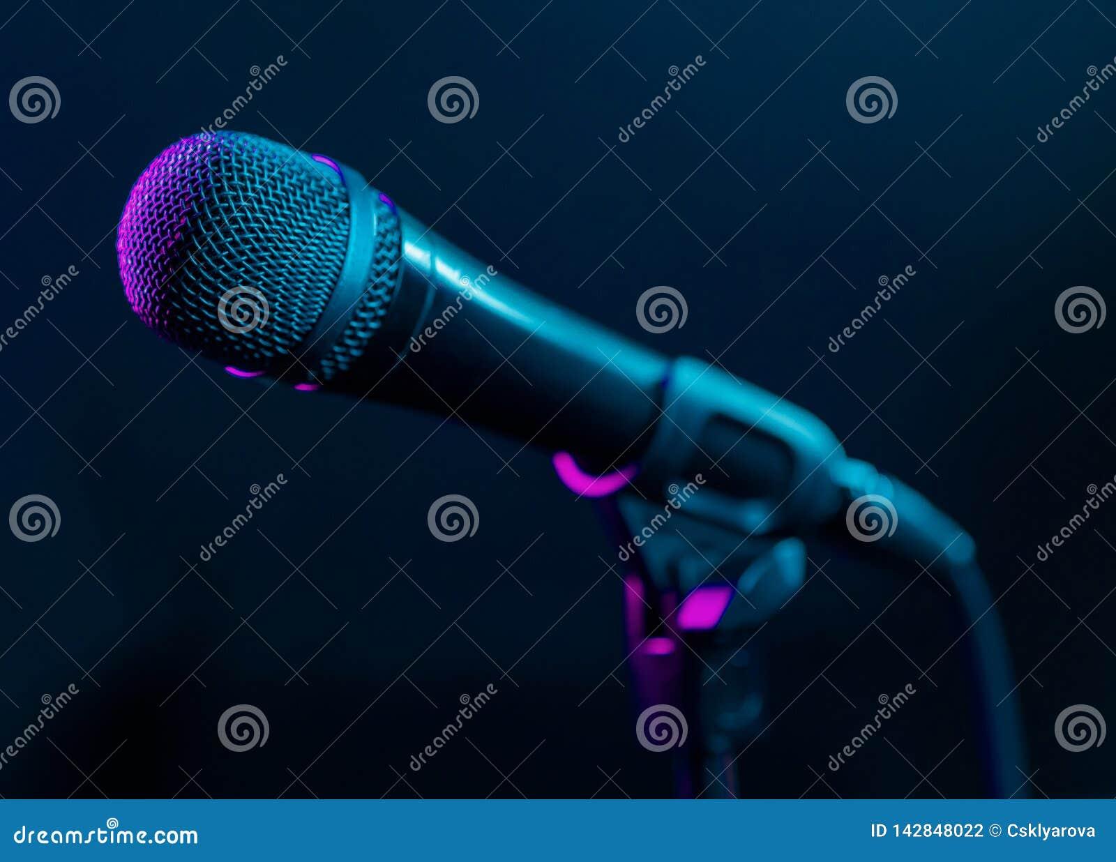 Mikrofon na czarnym tle z kolorowymi menchiami i turkus zaświecamy Muzyka, koncertowy pojęcie