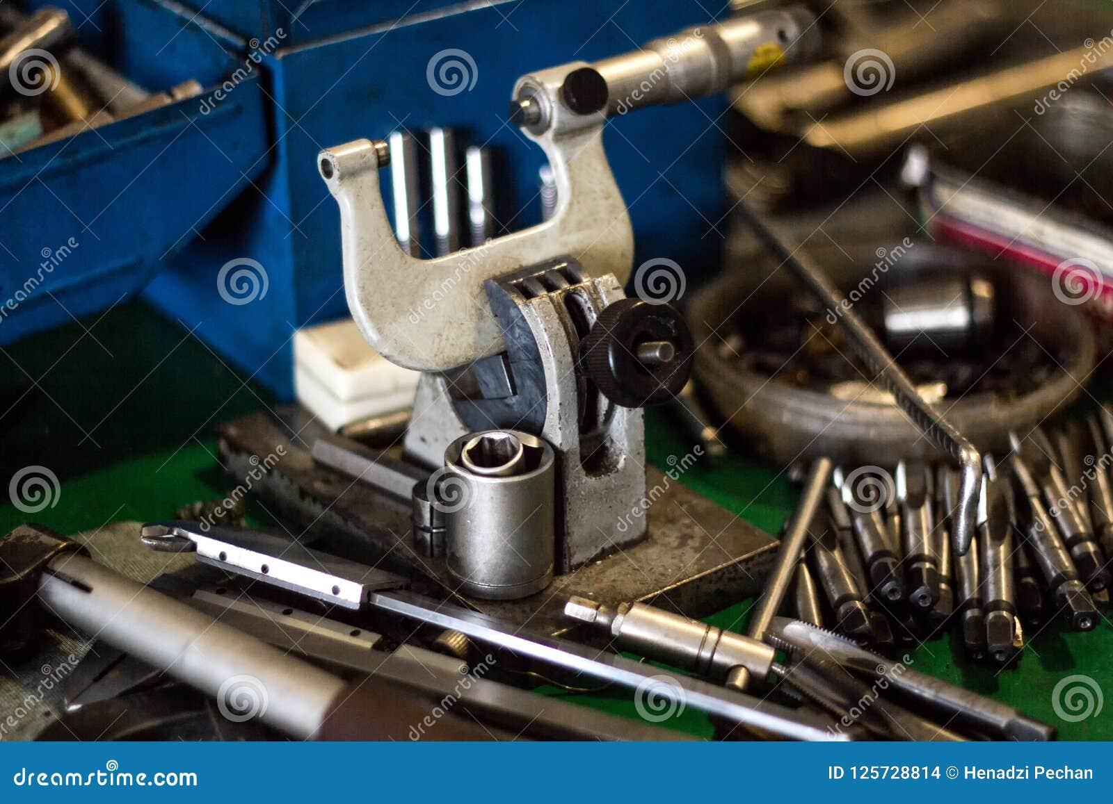 Mikrometer und andere Werkzeuge für Metalllüge auf dem Tisch bohren und schneiden, Nahaufnahme, stellend her