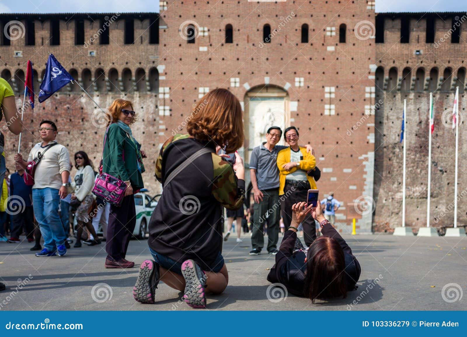 Milaan, Italië - September 28: De niet geïdentificeerde Aziatische toeristen maken foto s voor Castello Sforzesco op 28 September