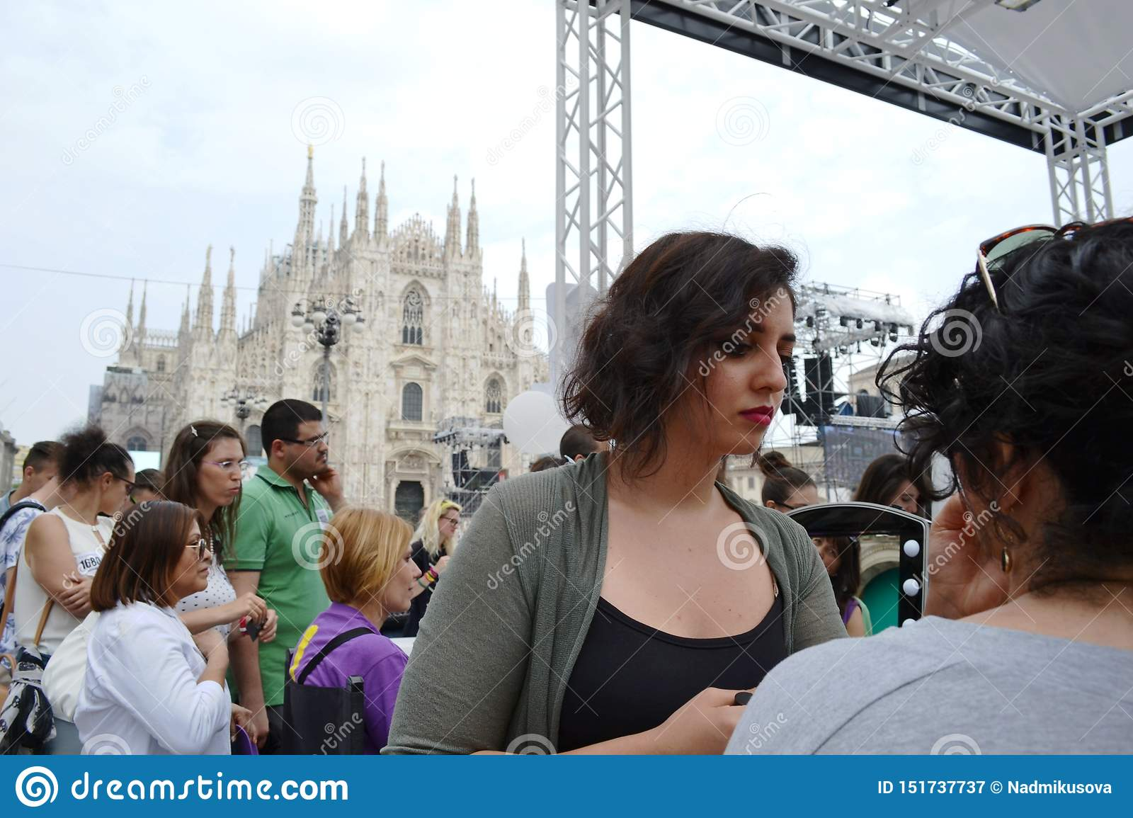 Beauticians receiving customers for free outdoors photo set `Brosway` in Milan Duomo square.