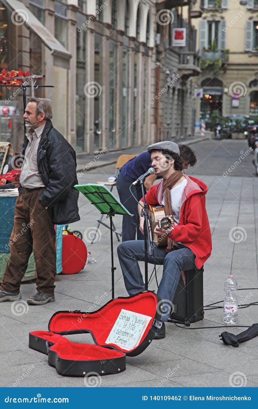 Milano, Italia - maggio 2017: Il musicista della via gioca la chitarra e canta in microfono Altro un uomo sistema l attrezzatura
